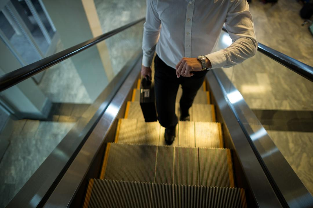 Commuter looking time while walking on escalator in airport