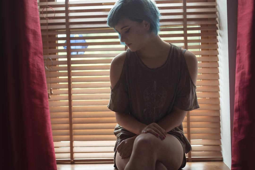 Thoughtful young woman looking down while sitting at window sill in bedroom