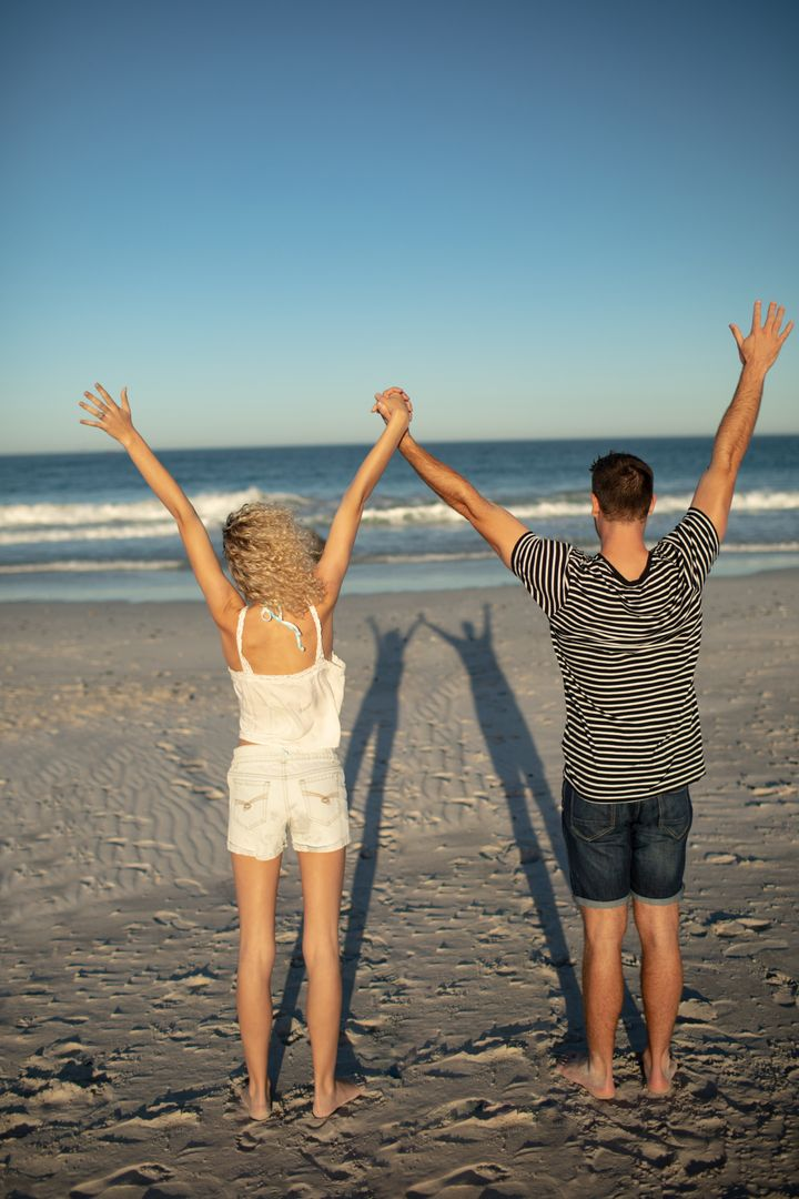 Rear view of couple standing together with arms up on the beach