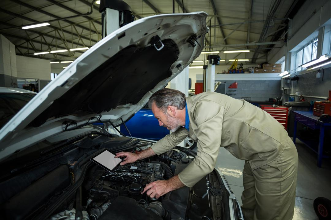 Mechanic using digital tablet while servicing a car engine at repair shop