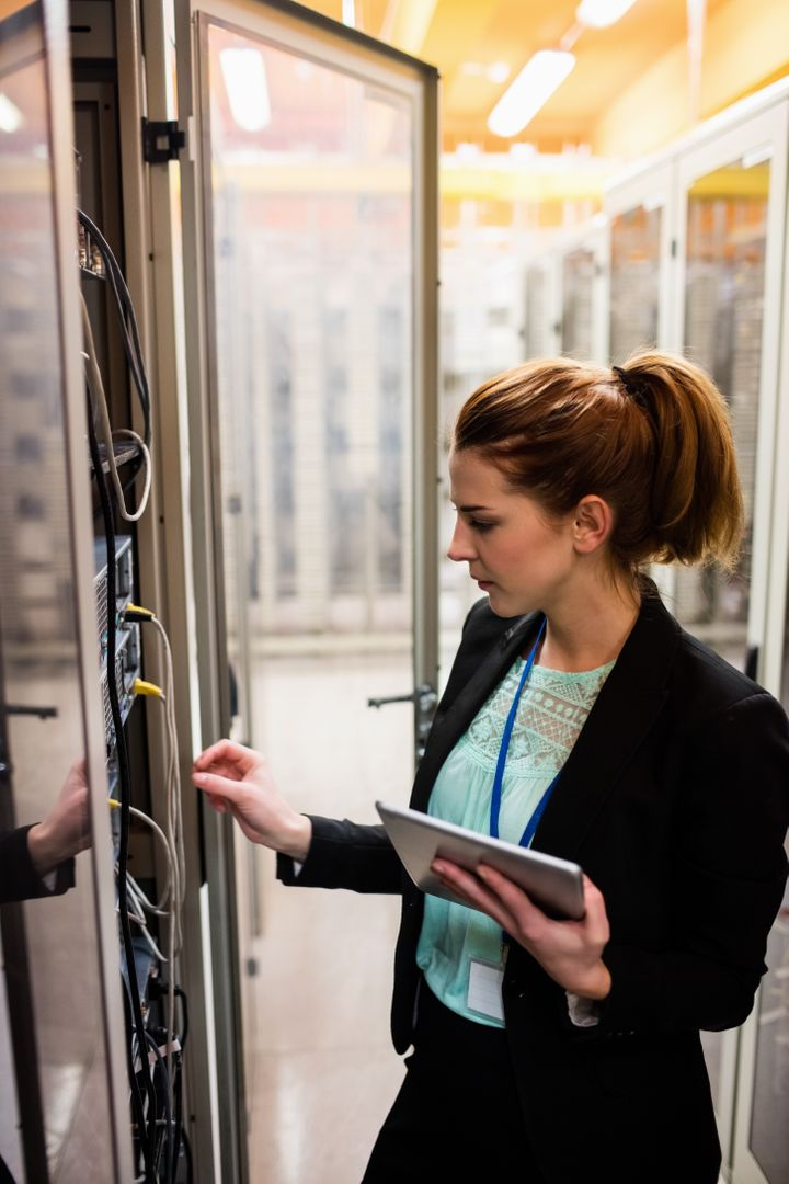 Technician holding digital tablet while examining server in server room Free Stock Images from PikWizard