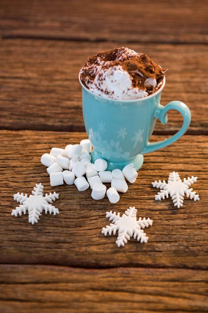 Cup of coffee with snowflake and marshmallow on wooden plank during christmas time Free Stock Images from PikWizard