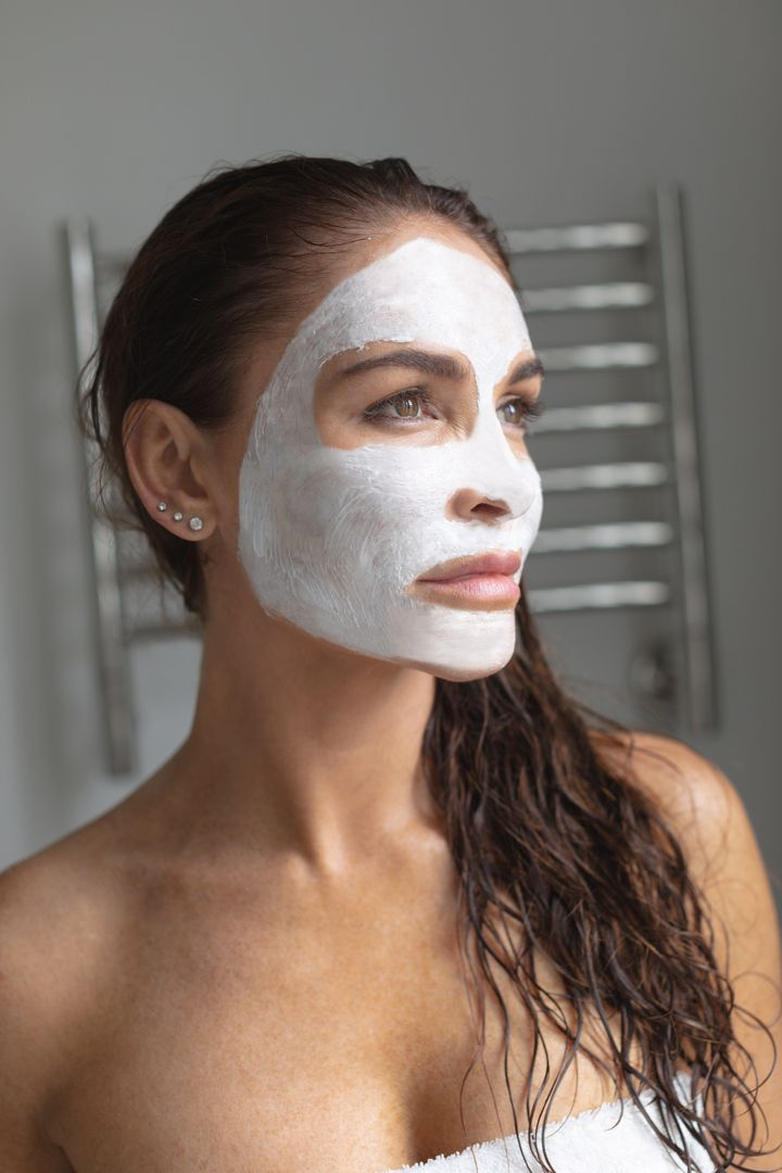 Thoughtful woman with facial mask standing in bathroom at home