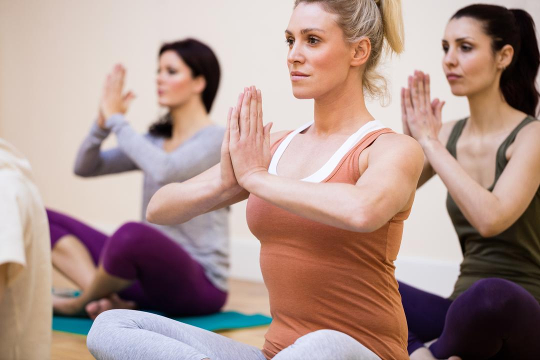 Women sitting in lotus position in the fitness studio