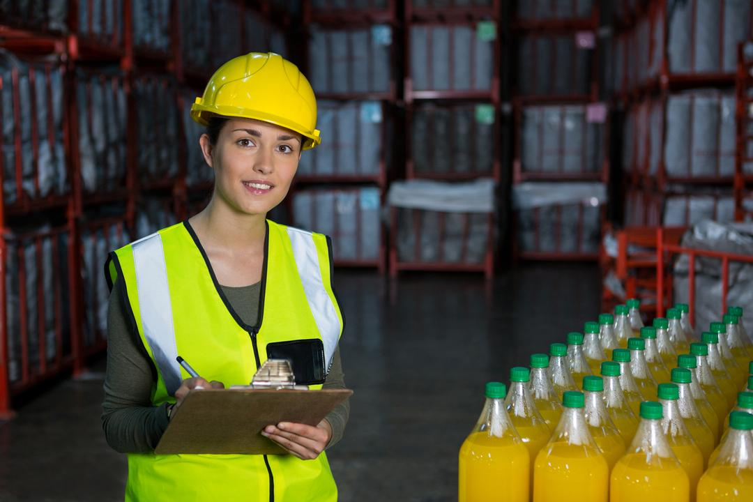 Young female worker checking juice bottles in factory