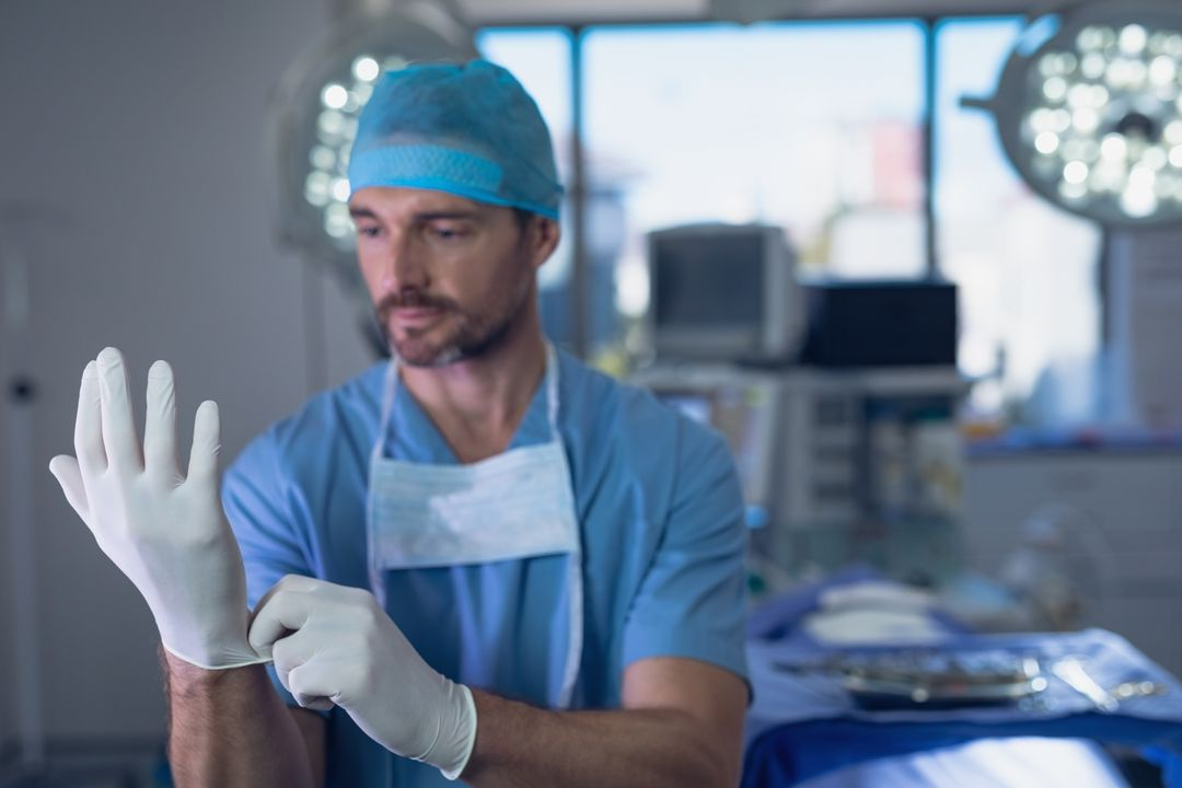 Male surgeon wearing surgical gloves in operation room at hospital