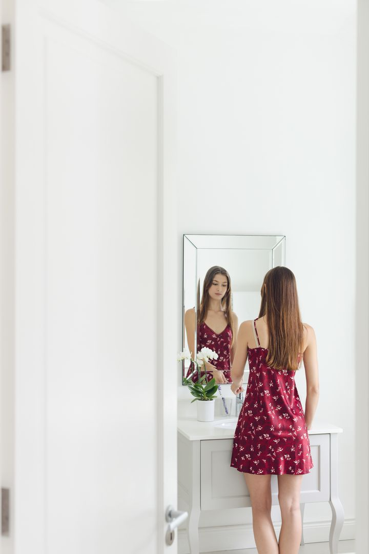 Beautiful woman standing in front of bathroom mirror in a comfortable home