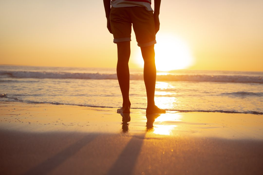 Low section of thoughtful man standing with hands in pocket on the beach Free Stock Images from PikWizard