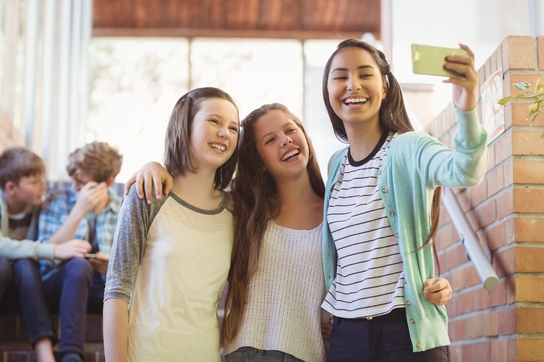 Smiling schoolgirls taking selfie with mobile phone in corridor at school