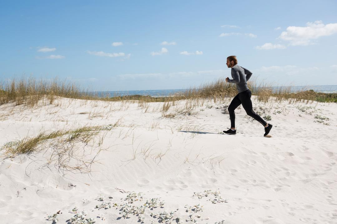 Male athlete running at beach against sky Free Stock Images from PikWizard