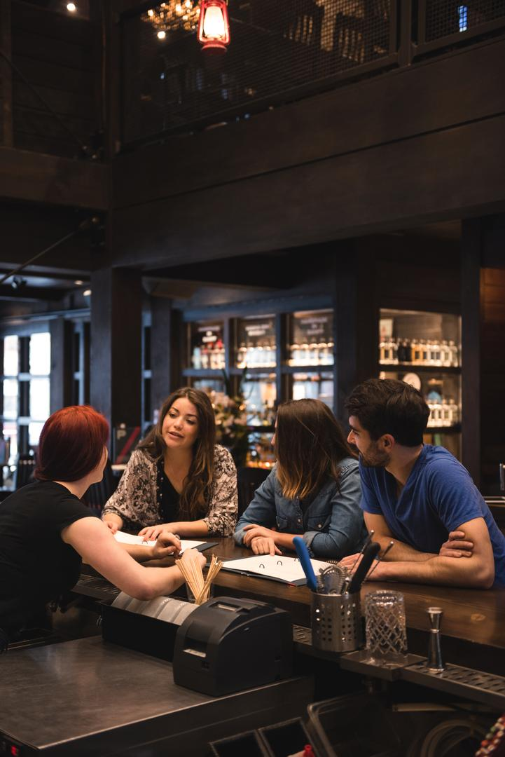 Bartender interacting with customers at bar counter