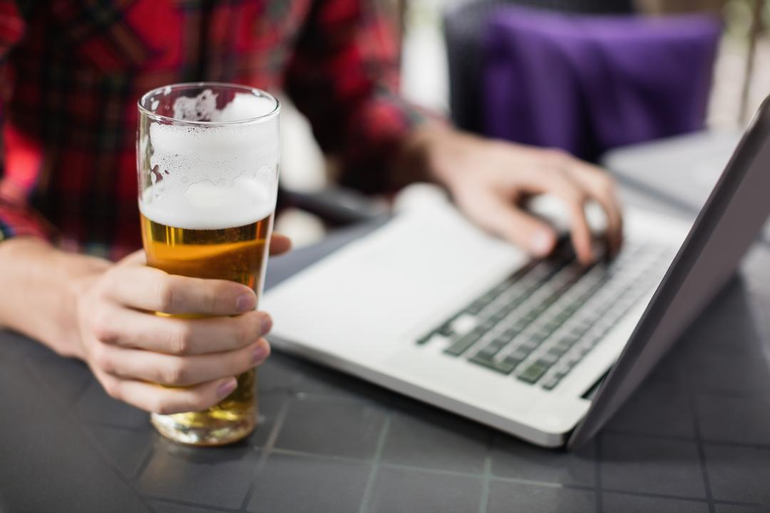 Mid section of man using laptop with glass of beer on table in bar Free Stock Images from PikWizard