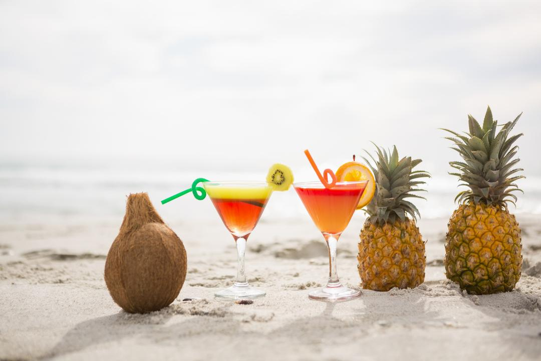 Coconut, pineapples and two glasses of cocktail drink kept on the sand at tropical beach