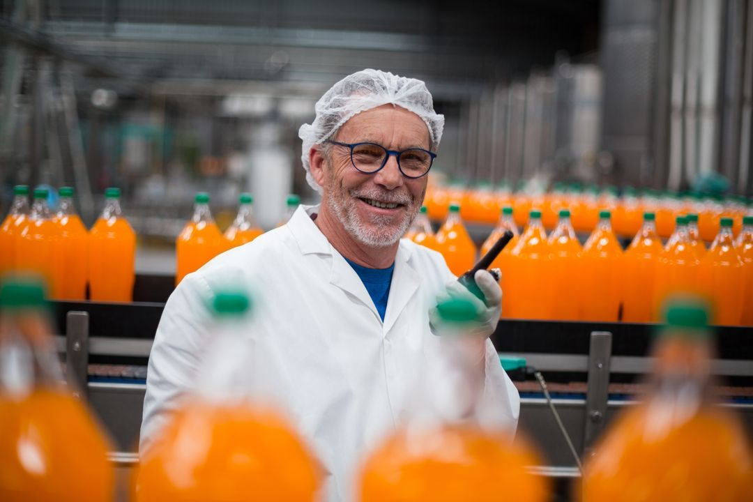 Portrait of smiling factory engineer standing near production line with walkie talkie in bottle factory Free Stock Images from PikWizard