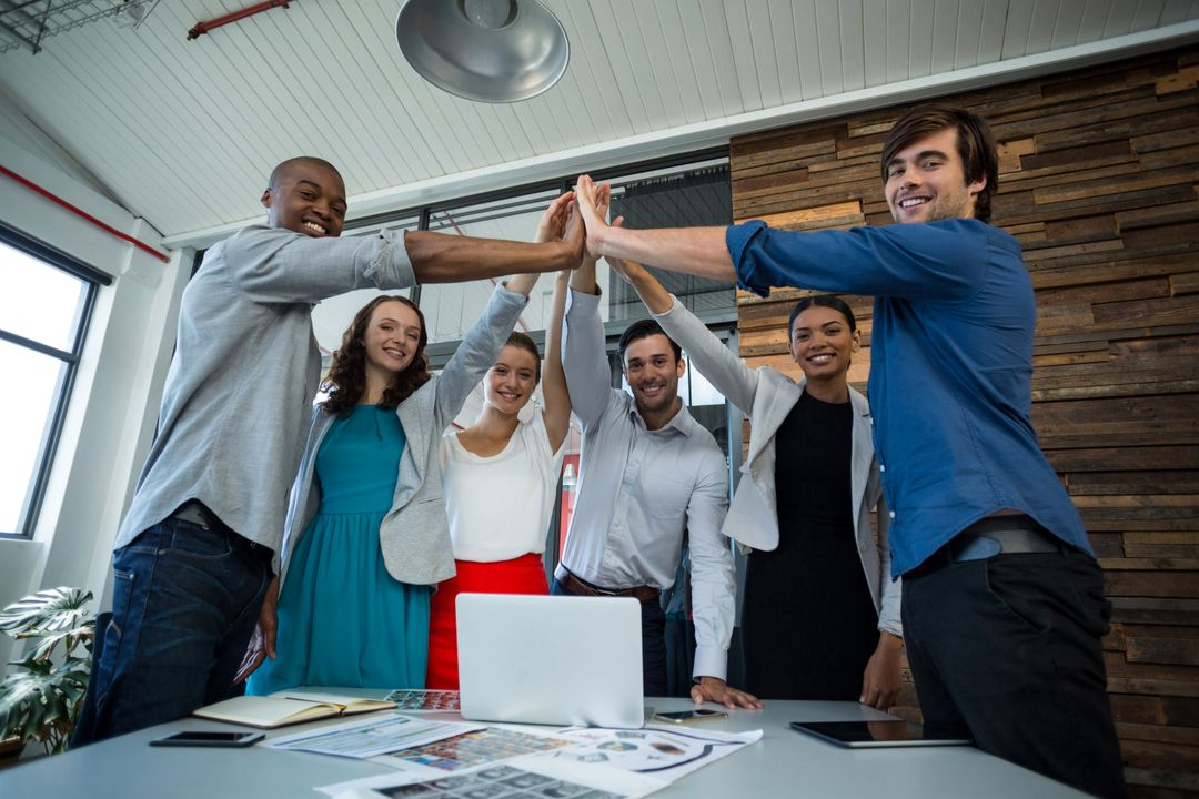 Team of graphic designers giving high five to each other in office Free Stock Images from PikWizard