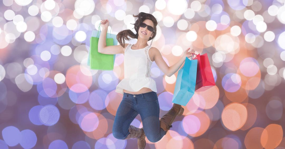 Digital composite of Woman with shopping bags jumping over bokeh