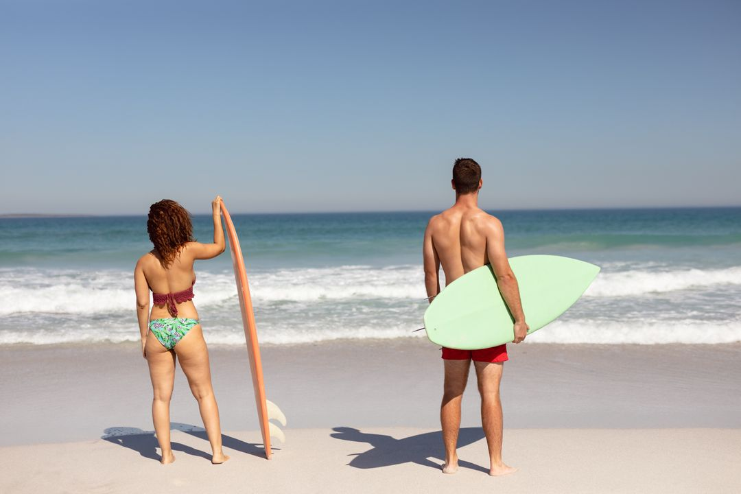 Rear view of diverse couple standing with surfboard on beach in the sunshine