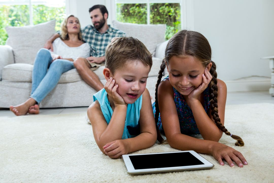 Children watching digital tablet screen while parents sitting on sofa in background Free Stock Images from PikWizard