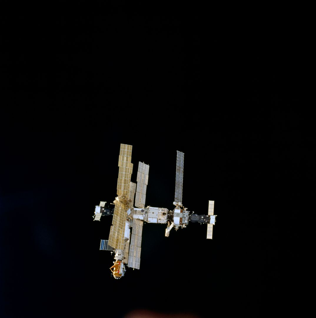 STS074-716-044 (18 Nov 1995) --- With the darkness of space providing the backdrop, this is the Russia?s Mir Space Station as seen from the Space Shuttle Atlantis, not long after the two spacecraft began their relative separation on November 18, 1995.  The new Docking Module (DM), delivered by Atlantis over three days earlier, is easily identified in the 70mm frame.  With five NASA astronauts aboard the Space Shuttle Atlantis, the flight began with a November 12, 1995, launch from Kennedy Space Center (KSC) and ended with landing there on November 20, 1995.  The STS-74 crew members were astronauts Kenneth D. Cameron, mission commander; James D. Halsell Jr., pilot; William S. McArthur Jr., Jerry L. Ross and Canadian astronaut Chris A. Hadfield, all mission specialists.  On November 15, 1995, the Space Shuttle Atlantis docked with the Mir Space Station, on which the STS-74 astronauts joined the Mir-20 crew.  The Mir-20 crew is composed of cosmonauts Yuriy P. Gidzenko, commander; and Sergei V. Avdeyev, flight engineer; along with the European Space Agency?s (ESA) Thomas Reiter, cosmonaut researcher.  Joint activities on the Mir Space Station and the Space Shuttle Atlantis ended November 18, 1995, when the two spacecraft separated.