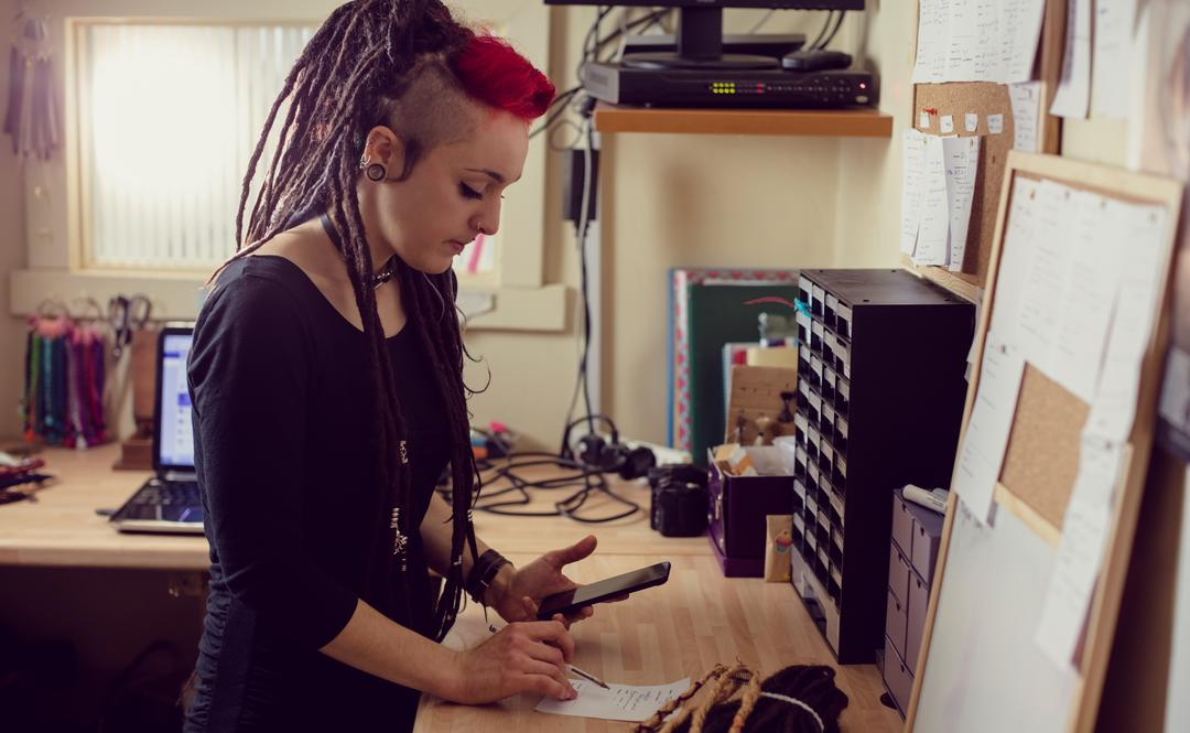 Female hairdresser using mobile phone and making notes in dreadlocks shop