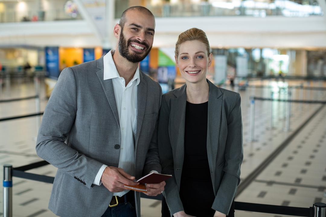 Portrait of smiling businesspeople with passport waiting in queue at airport terminal