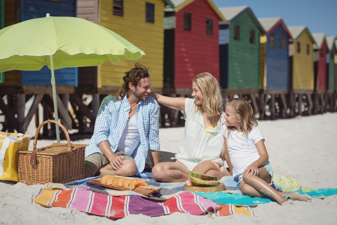 Happy family sitting on blanket at beach during sunny day Free Stock Images from PikWizard