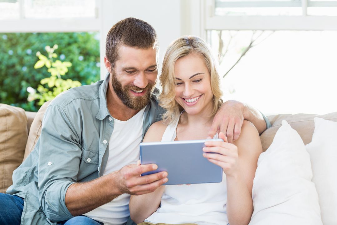 Happy couple sitting on sofa using digital tablet in living room at home