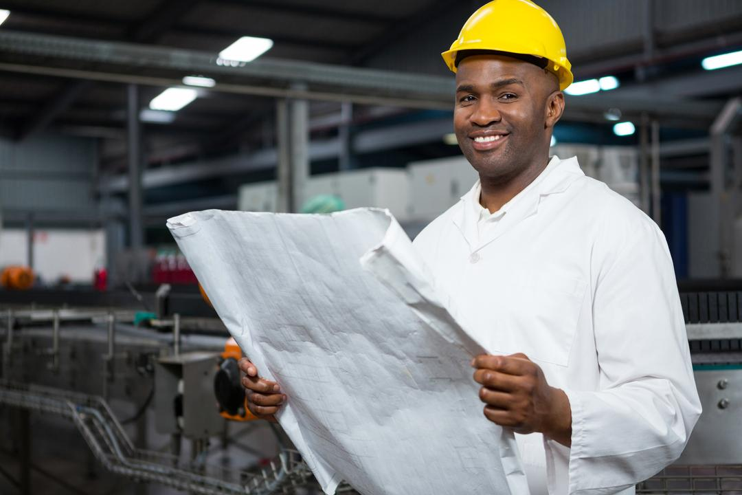 Portrait of smiling male worker reading instructions at juice factory Free Stock Images from PikWizard