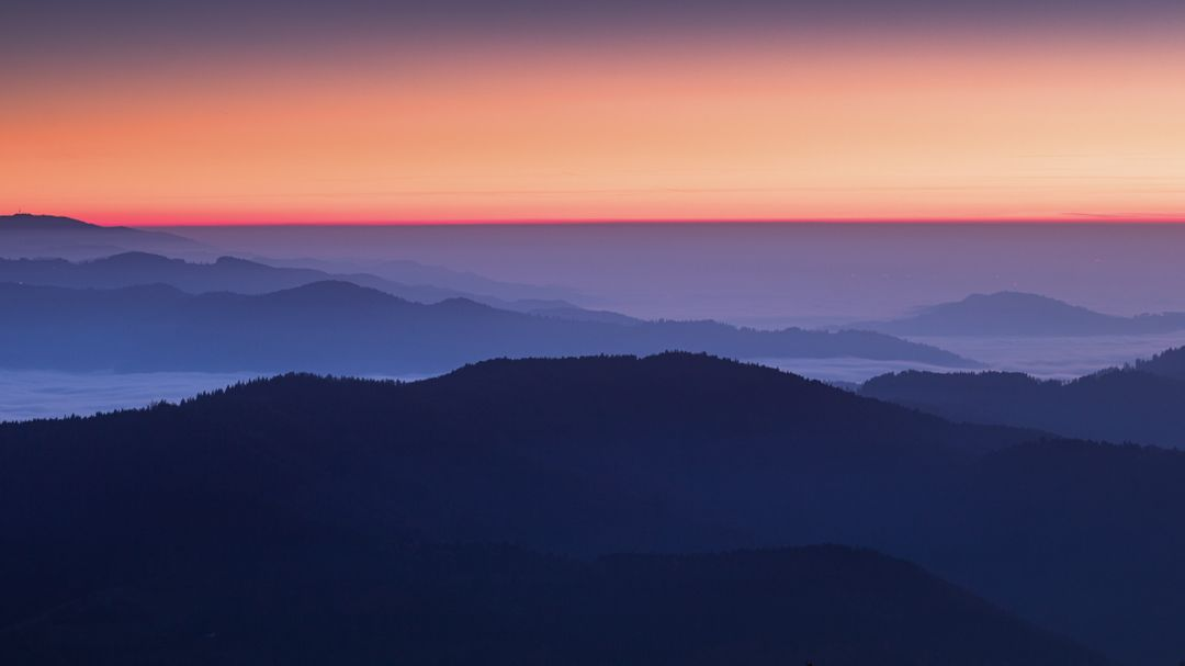 Image of a blue, purple and pink sunset behind a mountain landscape