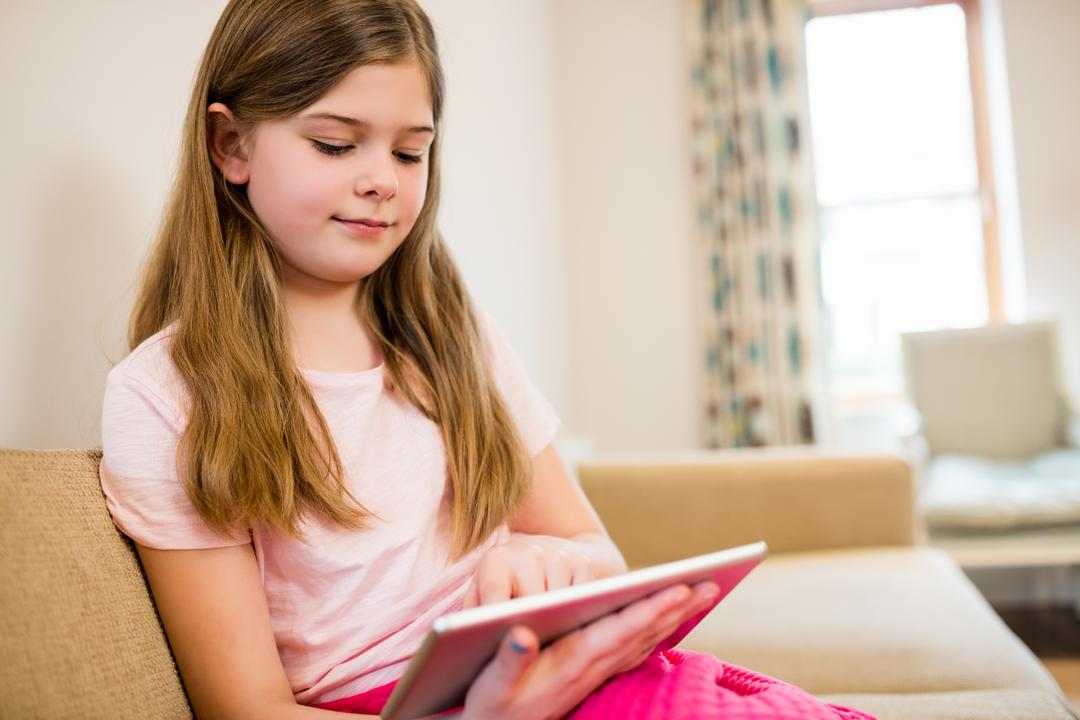 Girl sitting on sofa using digital tablet in living room at home