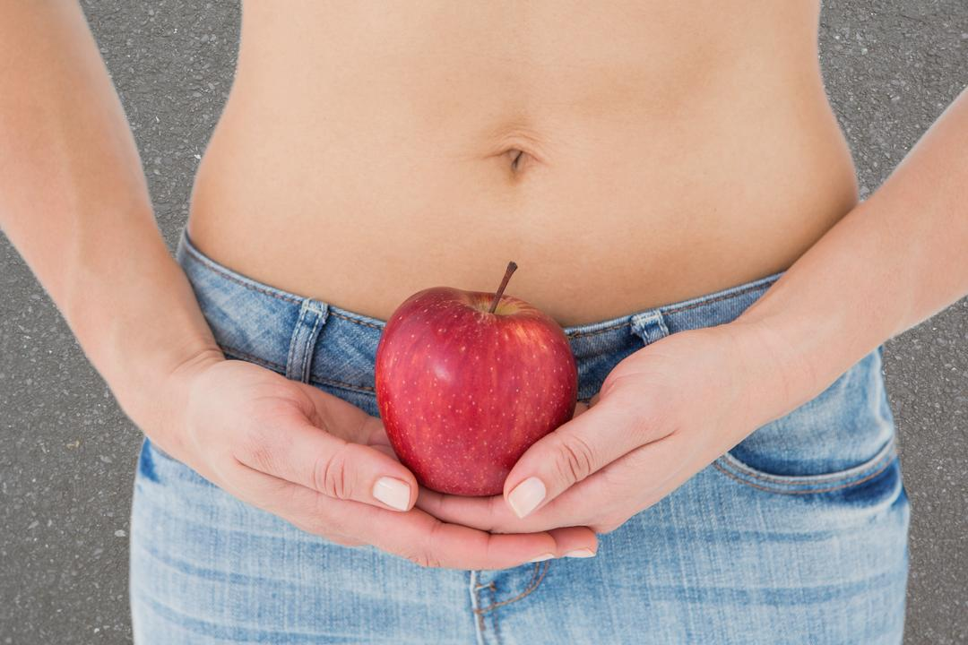 Midsection of woman holding apple representing weight loss