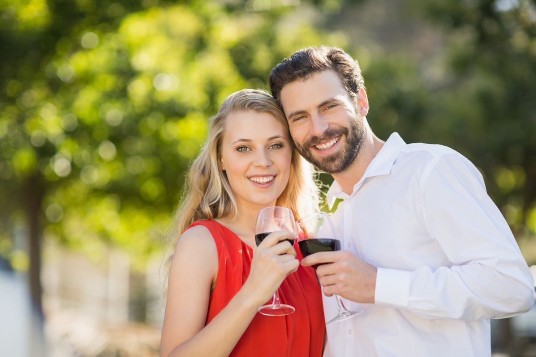 Portrait of happy couple holding wine glasses in the park Free Stock Images from PikWizard