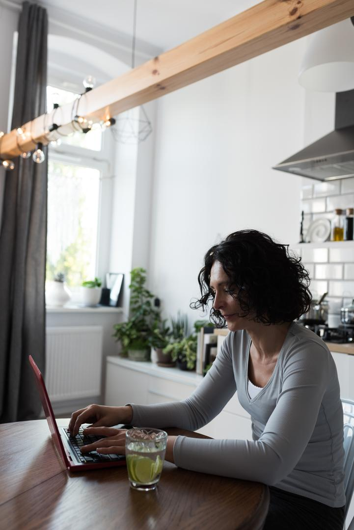 Attentive woman using laptop in kitchen at home