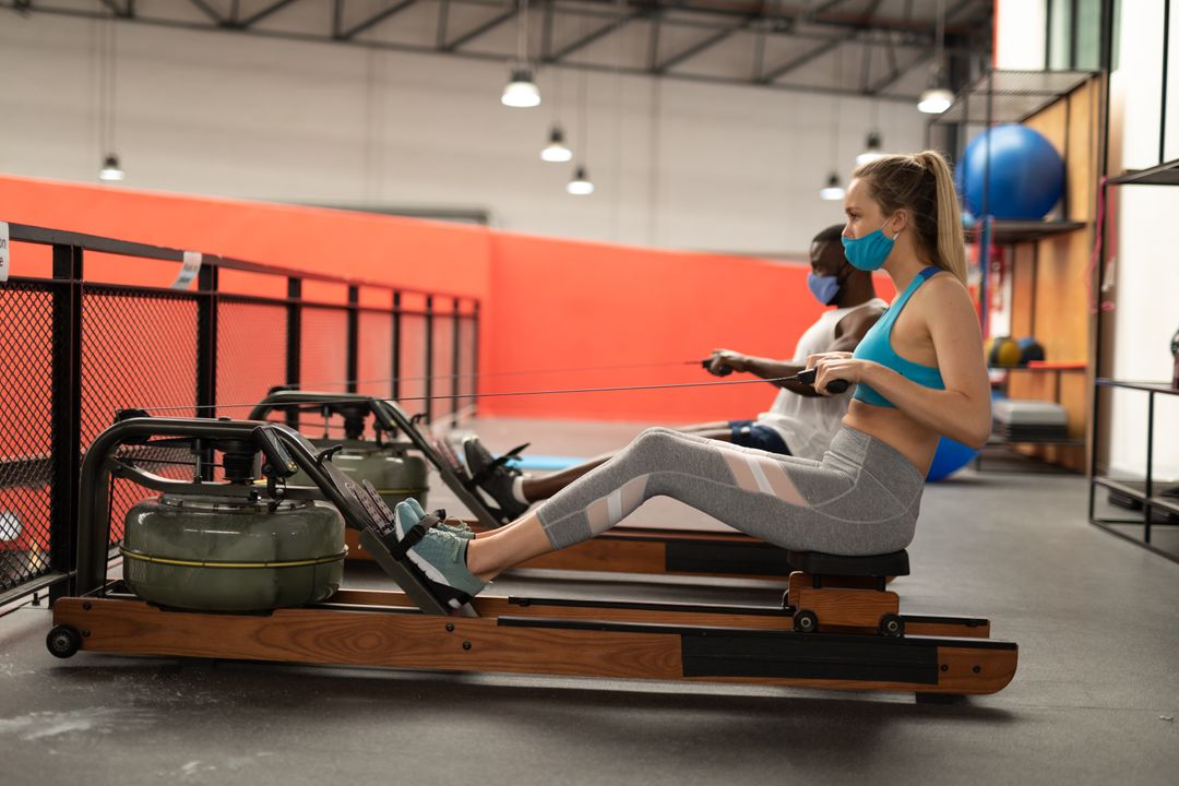 Caucasian woman and an african american man working out on the rolling seat exercise machine. Both of them are wearing facemasks. Free Stock Images from PikWizard