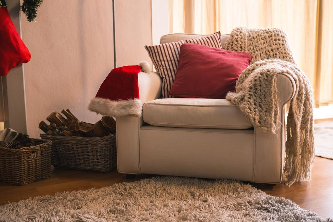 Woolen blanket, pillow and santa hat on sofa chair in living room at home