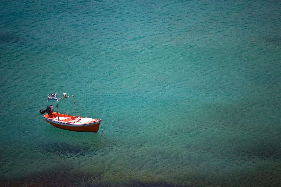 Image of red boat on dark teal water