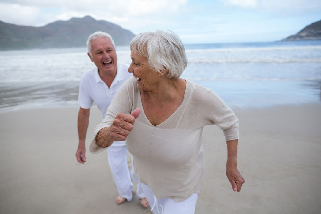 Happy senior couple having fun together at beach Free Stock Images from PikWizard