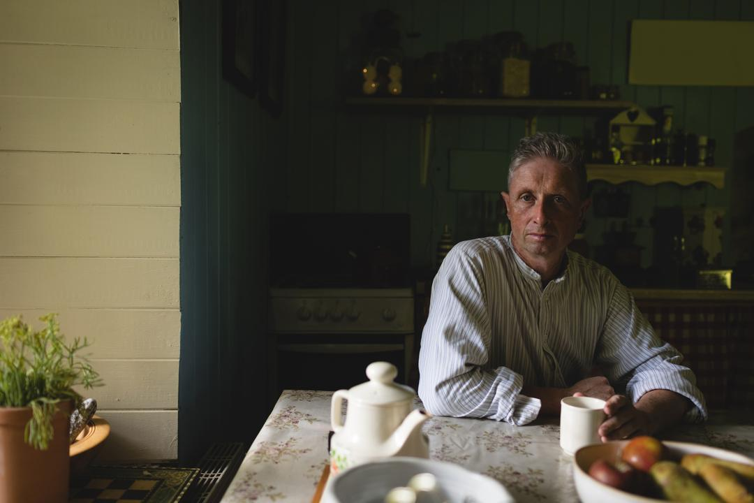Thoughtful senior man having coffee in kitchen at home