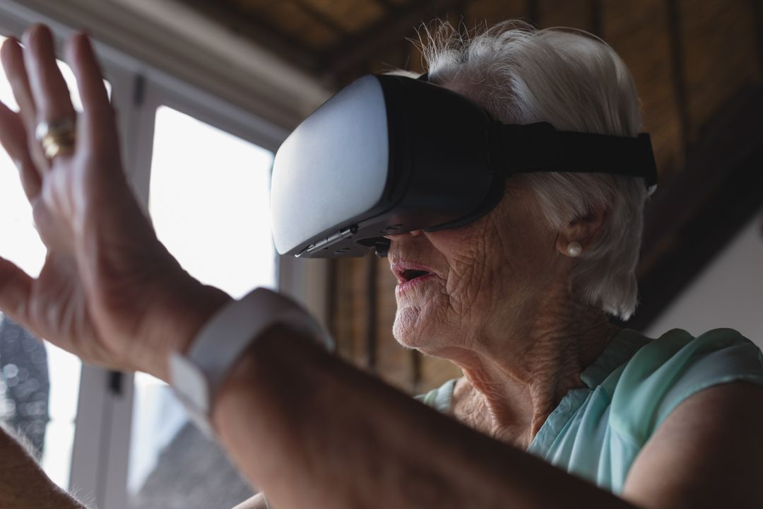 Close-up of a senior woman using virtual reality headset and raising her hand in living room at home Free Stock Images from PikWizard
