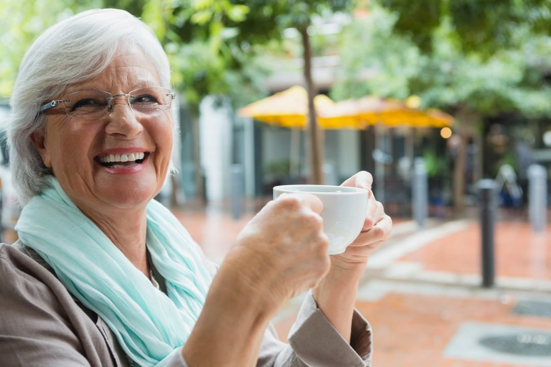Senior woman holding a coffee cup in outdoor cafe Free Stock Images from PikWizard