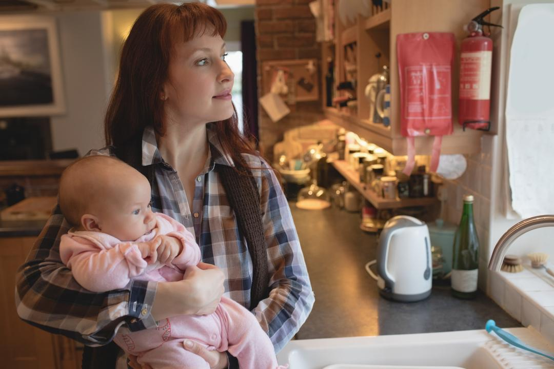 Thoughtful mother carrying her baby in kitchen at home