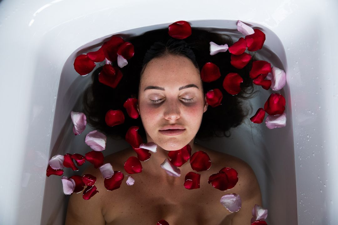 High angle front view of a young Caucasian brunette woman lying in a bath with rose petals in it, with closed eyes Free Stock Images from PikWizard