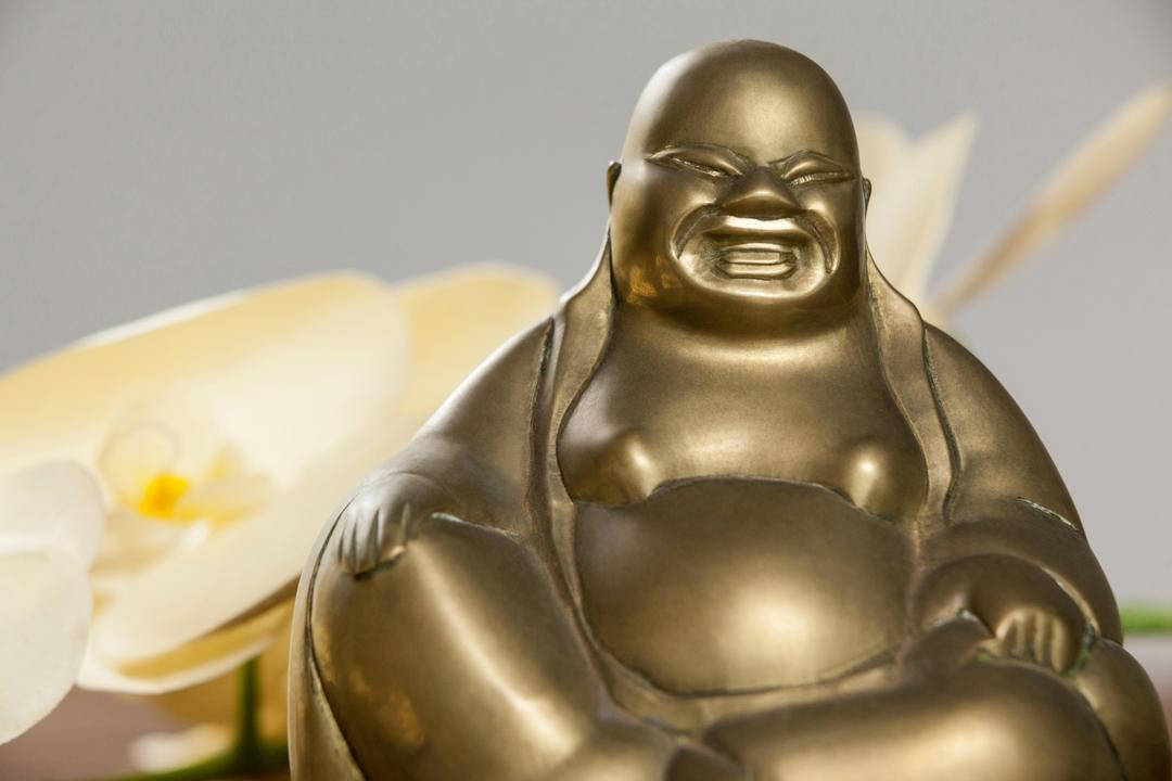 Gold painted laughing buddha figurine on wooden table Free Stock Images from PikWizard
