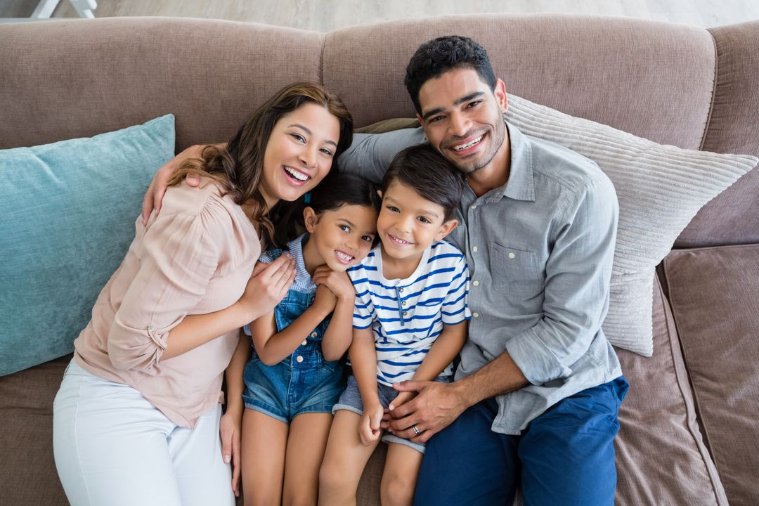 Portrait of happy parents and kids sitting on sofa in living room at home