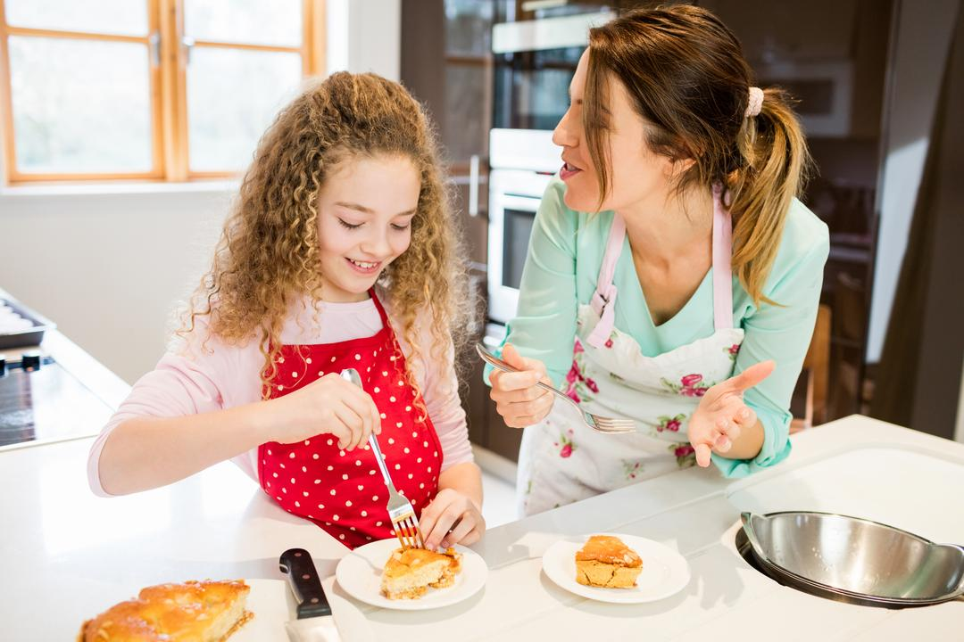 Mother and daughter eating pancake in kitchen at home