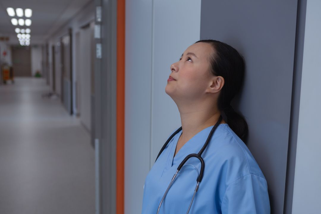 Side view of sad female doctor leaning against a wall in corridor at hospital