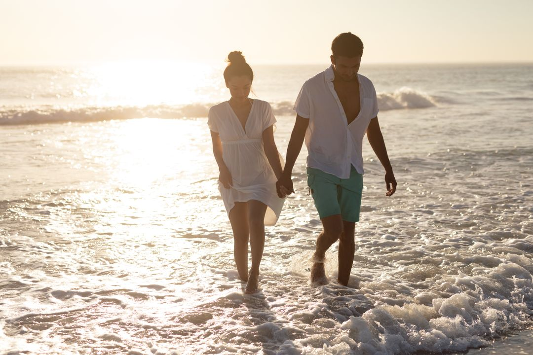 Romantic couple walking together hand in hand on the beach