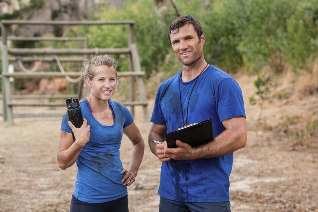 Trainer and woman standing together during obstacle course in boot camp Free Stock Images from PikWizard