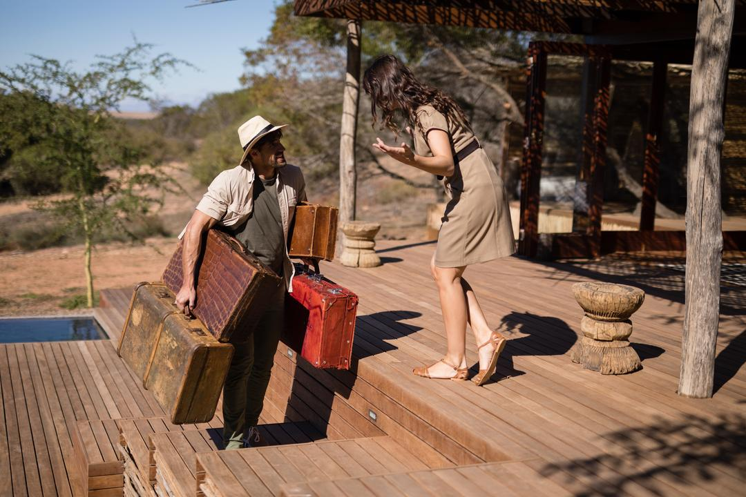 Woman gesturing while man carrying a suitcase during safari vacation