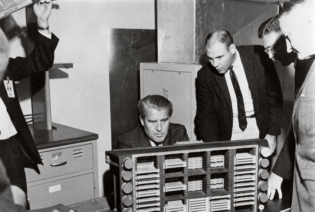 This photograph is dated March 10, 1966, and shows Dr. Von Braun (seated) examining a Saturn computer in the Astrionics Laboratory at the Marshall Space Flight Center. Standing left to right are J.B. White, Brooks Moore, and Herman K. Weidner. Free Stock Images from PikWizard